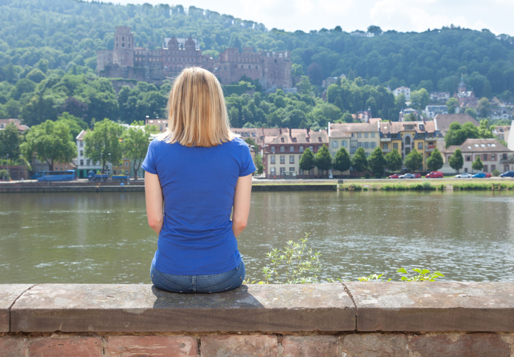 Young woman sitting on the riverside at Heidelberg