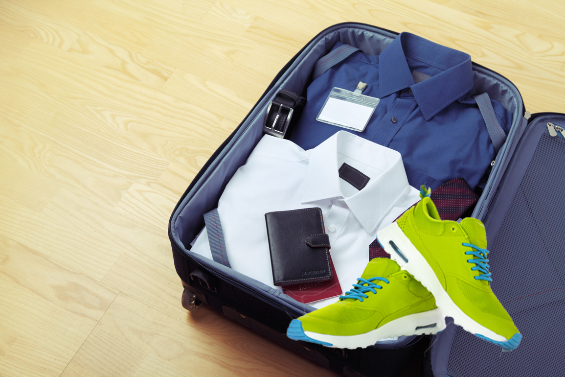 Image of businessman's clothes and documents in travel bag. White and blue shirts, belt, and necktie in travel bag with copyspace.