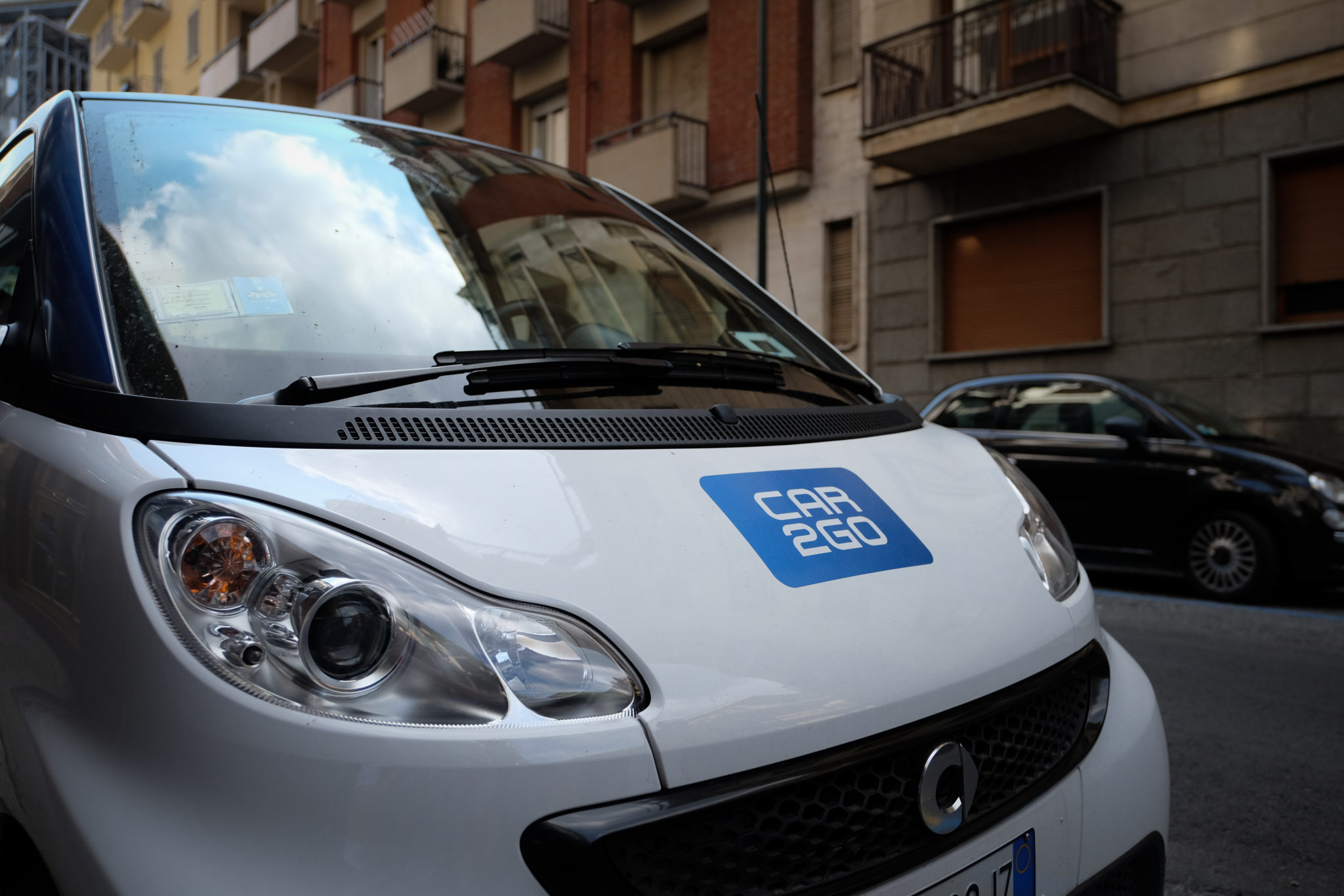"Turin, Italy - August 22, 2015: Detail of a parked Daimler Smart Vehicle from the ""Car2Go"" in Italy (Turin). Car2Go is a subsidiary of Daimler AG providing car-sharing services in European and North American cities."