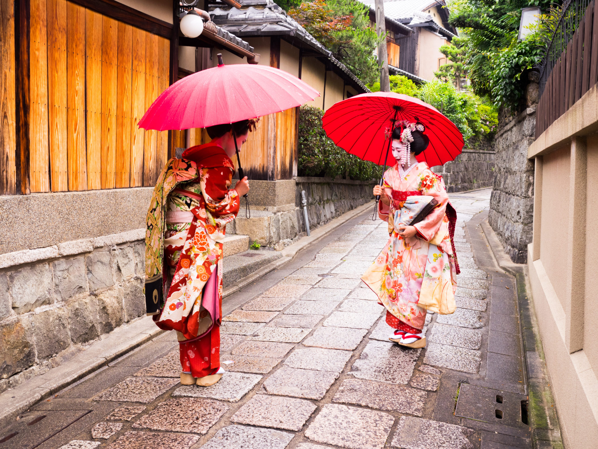 greeting of two young maiko ladies in the old street in Kyoto.
