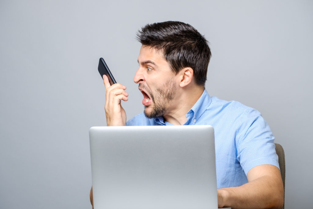 Portrait of angry young man screaming on his mobile phone over gray background