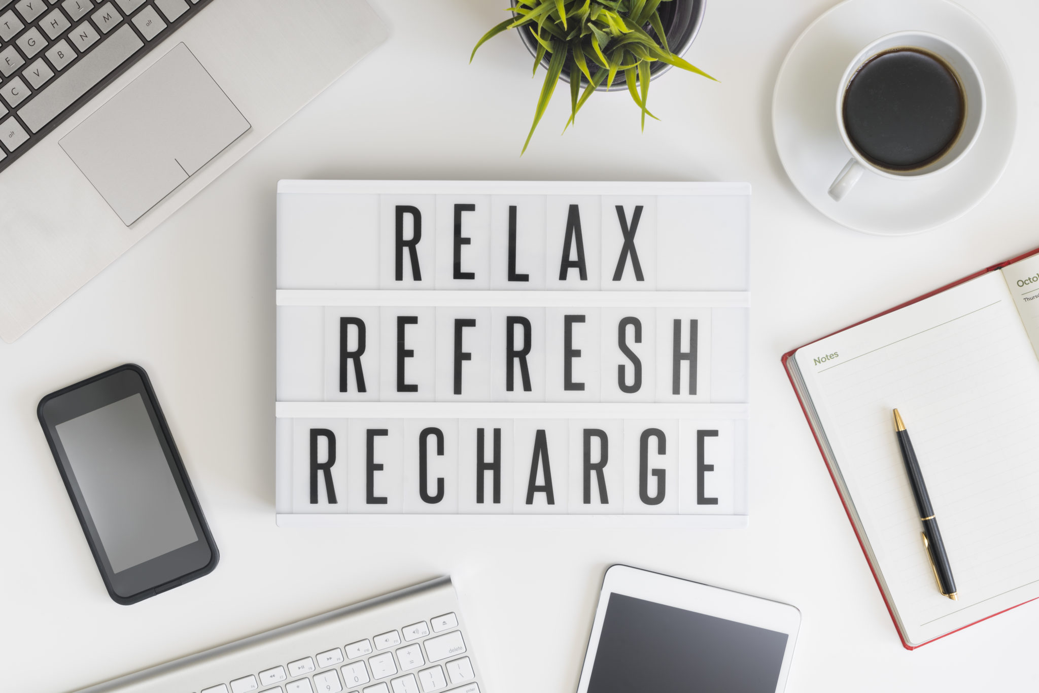 Relax, refresh and recharge words on office table with computer, coffee, notepad, smartphone and digital tablet